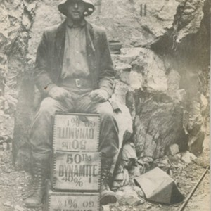 Miner sitting on dynamite boxes
